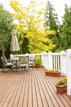Vertical photo of a large outdoor natural cedar deck with patio furniture and bright yellow and green trees in background