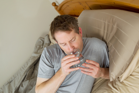 Horizontal photo of mature man drinking water in bed