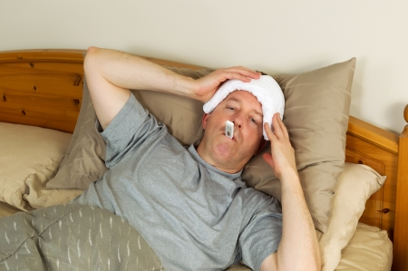 Horizontal photo of mature man holding wash cloth to his forehead along with thermometer in mouth while lying in bed