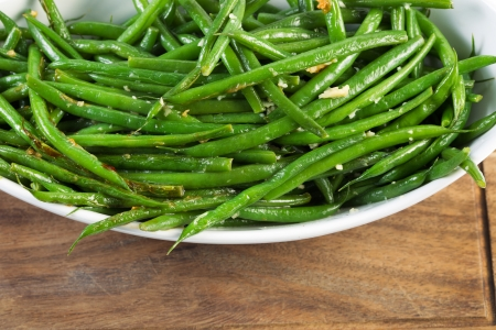 Horizontal shot of freshly cooked green beans in white bowl on black walnut serving board