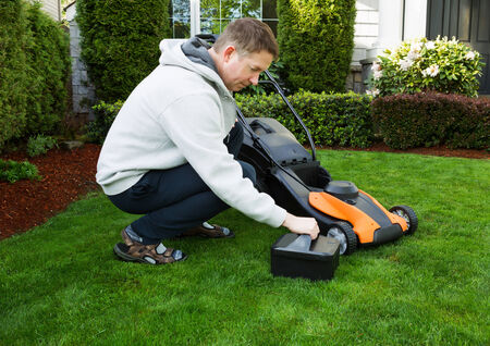 mature man putting in battery in electric lawnmower on freshly cut plush green grass with home in background
