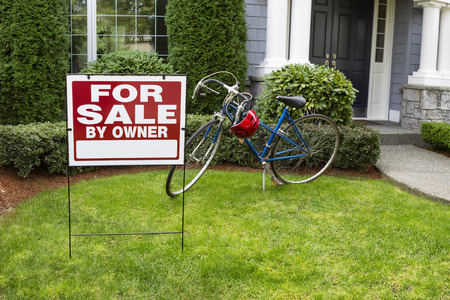 Closeup view of Modern Suburban Home with for Sale Real Estate Sign in front yard and bicycle and house in background