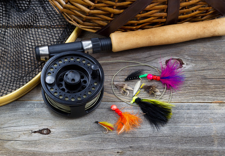 Photo pour Close up top view of  fishing fly reel, landing net, creel and assorted flies, with partial cork handled pole on rustic wooden boards - image libre de droit