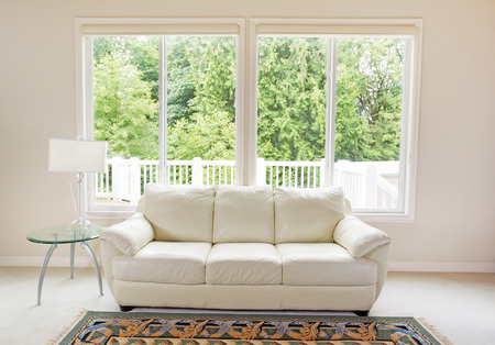 Photo pour Clean family room with white leather couch and large windows showing bright green trees in background. - image libre de droit