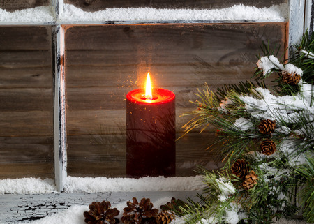 Photo pour Decorated window with glowing red candle, selective focus on flame and top part of candle, pine tree, cones and snow outside. Christmas concept. - image libre de droit