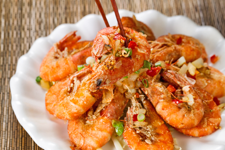 Photo pour Close up front view of a fried bread coated shrimp, selective focus on single piece in chopsticks, with fresh garnishes. - image libre de droit