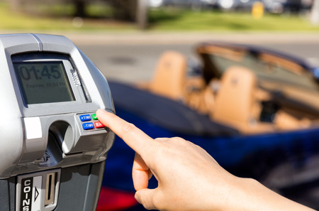 Close up of female hand, index finger, selecting parking meter time outdoors on street. Selective focus on tip of index finger and meter buttons.