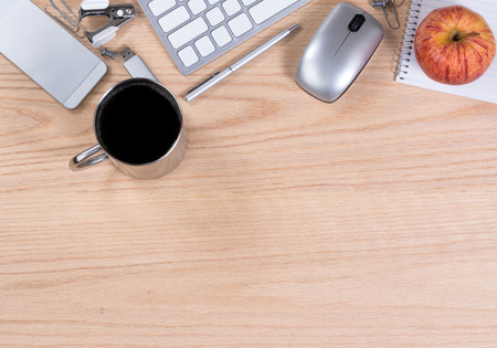 Working office desktop with computer keyboard, mouse, coffee, apple, thumb drive, pen, paper, clip, staple remover, and cell phone. Horizontal format with plenty of copy space