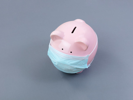 Foto de Piggy bank with surgical mask on face - Imagen libre de derechos