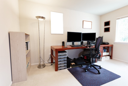 Foto de Comfortable computer chair at large work table with computer monitors and other technology equipment in bright home office interior - Imagen libre de derechos