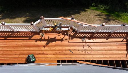 Foto de Overhead view of outdoor wooden deck being remodeled with power and hand tools on floor boards - Imagen libre de derechos