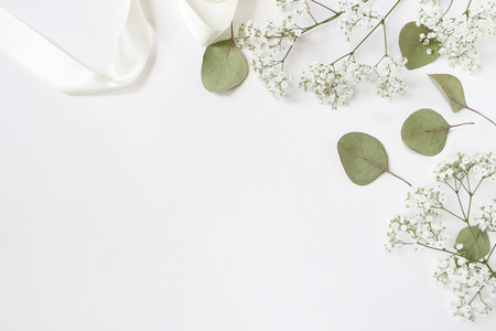 Styled stock photo. Feminine wedding desktop mockup with babys breath Gypsophila flowers, dry green eucalyptus leaves, satin ribbon and white background. Empty space. Top view. Picture for blog.