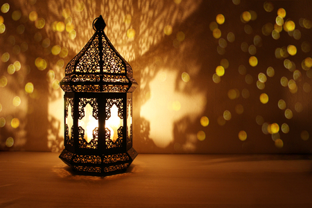 Photo for Ornamental Arabic lantern with burning candle glowing at night and glittering golden bokeh lights. Festive greeting card, invitation for Muslim holy month Ramadan Kareem. Dark background. - Royalty Free Image