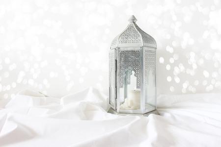 Photo pour Ornamental silver Moroccan, Arabic lantern on white linen throw. Burning candle, glittering bokeh lights. Greeting card for Muslim community holy month Ramadan Kareem. Festive background. - image libre de droit