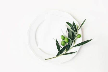 Photo pour Festive table summer setting with olive leaves, branch and fruit on porcelain plate. Blank paper card mockup scene. Mediterranean wedding or restaurant menu concept. Flat lay, top view. - image libre de droit