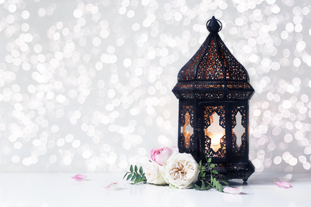 Vintage black Moroccan, Arabic lantern with glowing candle, green branches, rose flowers and petals on white table background. Greeting card for Muslim holiday Ramadan Kareem with bokeh lights.