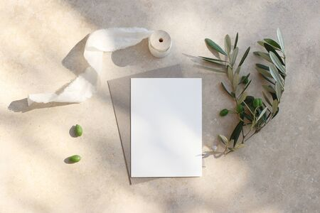 Photo pour Summer wedding stationery mock-up scene. Blank greeting card, invitation. Craft envelope, olive fruit, branch and silk ribbon. Elegant marble background in sunlight, shadows. Flat lay, top view. - image libre de droit