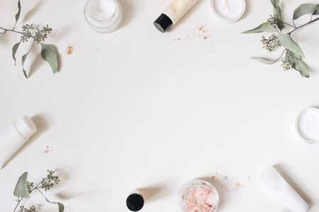 Photo pour Skin cream, shampoo bottle, dry eucalyptus leaves and pink Himalayan salt. White table background. Styled beauty frame, web banner. Organic cosmetics, spa concept, empty space, flat lay, top view. - image libre de droit