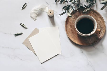 Foto de Summer wedding stationery mock-up scene. Blank greeting cards, wooden plate, envelope, ribbon, cup of coffee and olive branches. White marble stone table background. Feminine flat lay, top view. - Imagen libre de derechos