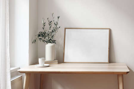 Photo pour Home office concept. Empty horizontal wooden picture frame mockup. Cup of coffee on wooden table. White wall background. Vase with olive branches. Elegant working space. Scandinavian interior design. - image libre de droit