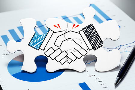 Photo for Handshake jigsaw puzzle pieces on report. Concept image of business partnership and agreement. - Royalty Free Image