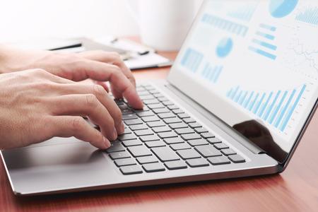 Photo pour Business analytics concept. Businessman preparing reports. Laptop and many graphs. - image libre de droit
