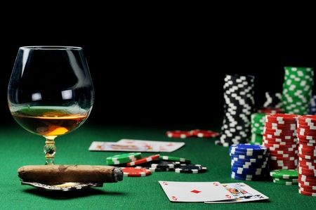 Cigar, chips for gamblings, drink and playing cards on green