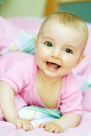 Foto de  cheerful baby lies on stomach - Imagen libre de derechos