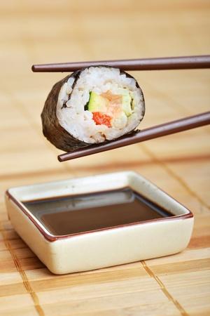 sushi between chopsticks ready to dip into  sauce