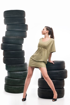 Young sexy woman like vulcaniser with a automobile tire