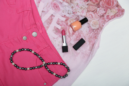 Girl accessories lipstick, nail polish and necklace on bright pink clothes