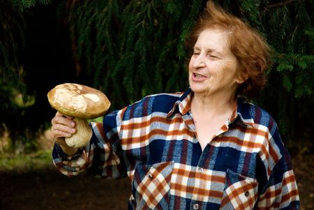 Old woman is proudly showing her trophy - large mushroom