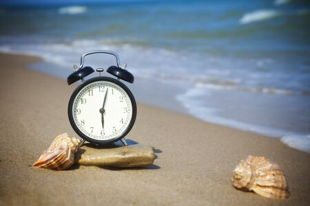 Time to relax! The sea is calling!  The alarm and seashells on the shore of the warm sea