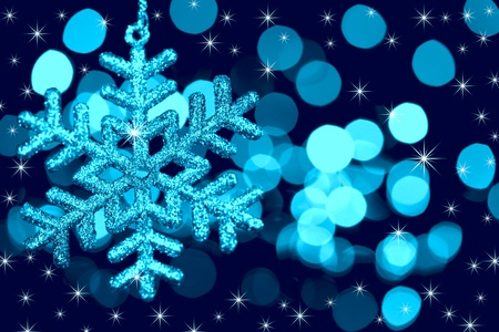 Christmas decoration snowflake  on defocused lights and stars background / blue toned