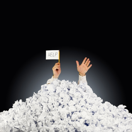 Foto de Person under crumpled pile of papers with hand holding a help sign  - Imagen libre de derechos
