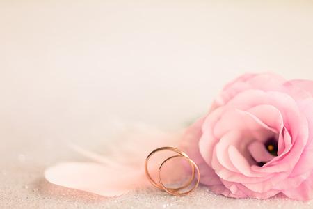 Foto de Wedding  Background with gold Rings, Eustoma rose flower and light pink feather - Imagen libre de derechos