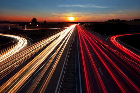 Foto de Speed Traffic  light trails on highway at sundown time,  long exposure, urban background with sun and dark sky - Imagen libre de derechos