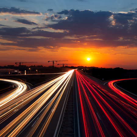 Foto de Speed Traffic at Sundown Time in the city - light trails on motorway highway at dusk,  long exposure, urban background - Imagen libre de derechos