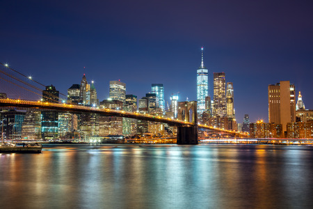 New York -  view of Manhattan Skyline with skyscrapers  and famous Brooklin Bridge by night and city illumination, USA