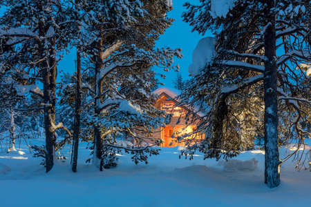 Photo for Winter fairytale landscape - Wooden house with warm light in night snowy winter forest, big size - Royalty Free Image