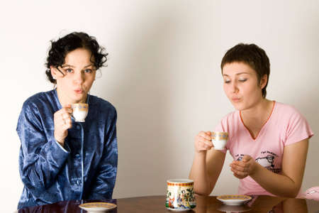 two young woman sitting at a table and drinking tea