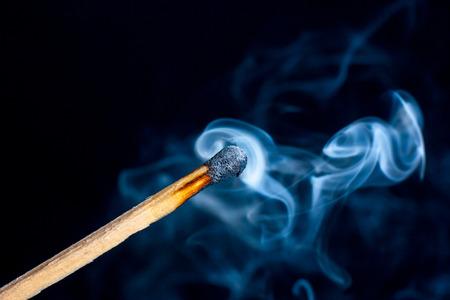 Burning match isolated on black background with smoke clouds. Macro photo.