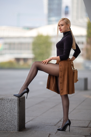 Foto de Beautiful blonde girl with perfect legs in pantyhose and shoes with high heels posing outdoor on the city square. - Imagen libre de derechos