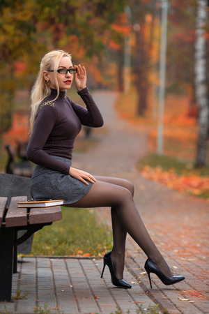 Photo pour Beautiful student girl with perfect legs sitting on the bench in the autumn park. - image libre de droit
