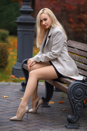 Foto de Beautiful girl in the coat with perfect legs sitting on the bench in the autumn park. - Imagen libre de derechos