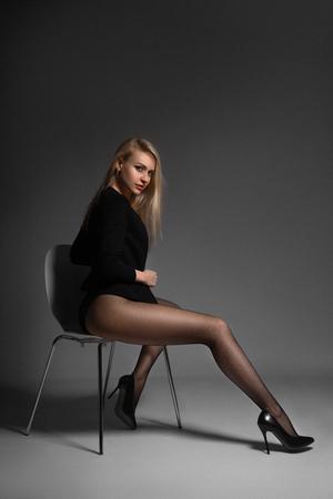 Foto de Beautiful blonde woman posing in black net pantyhose on the gray background. - Imagen libre de derechos