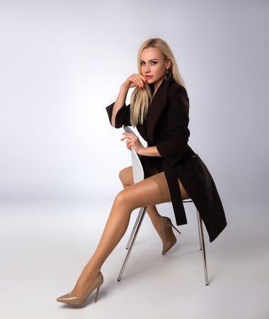 Foto de Beautiful blonde woman posing in nude color stockings on the gray background. - Imagen libre de derechos