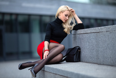 Foto de Beautiful blonde girl in red skirt with perfect legs in pantyhose and shoes with high heels posing outdoor on the city square. - Imagen libre de derechos