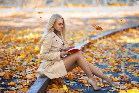 Foto de Beautiful student girl with perfect legs sitting on the bench and reading the book in the autumn park in the lights of setting sun. - Imagen libre de derechos
