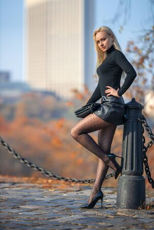 Photo for Beautiful blonde woman posing outdoor in the autumn park in the lights of setting sun. - Royalty Free Image